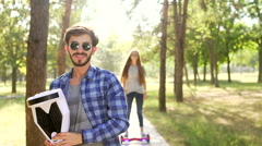 Handsome man standing with gyroscooter and girl come over and kiss  Stock Footage