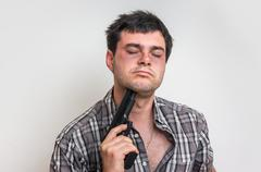 Depressive man trying to commit suicide with a gun aiming on his head Stock Photos