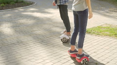 Young man and woman riding on the Hoverboard in the park. content technologies.  Stock Footage
