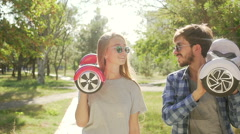 Modern couple walking with hoverboard. Kidding  and kissing.   Stock Footage