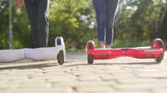 Young man and woman came over to Hoverboards and starts ridding.  Stock Footage