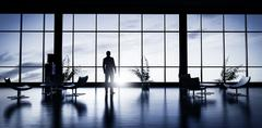 Business man standing in the office looking out of the window at sunset sky. Stock Illustration
