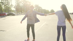 Young man and woman having fun with Hoverboard. A new movement. Wide shot.  Stock Footage