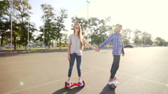 Modern young man and woman walking with Hoverboard. A new movement. Wide shot. Stock Footage