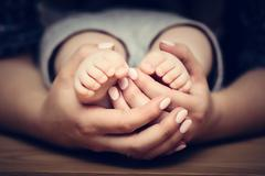Little baby feet in mother's hands. Child care, feeling safe, protect. Stock Photos