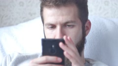 A young bearded man uses his mobile phone. Close-up shot, focus on eyes Stock Footage