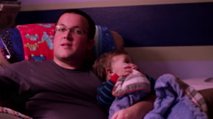 A father turns out the lights after reading his little boy a book before bed Stock Footage