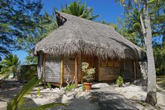 Wooden tropical bungalow with thatched roof Stock Photos