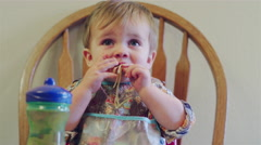 Baby sitting in a booster seat and eating spaghetti with his hands Stock Footage