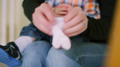 A mother putting socks on her baby boy as he sits on her lap Stock Footage
