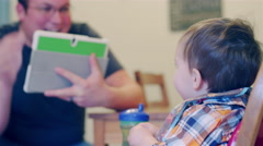 A father with a tablet taking photos of his baby eating in a booster seat Stock Footage