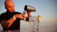 Young professional bartender preparing cocktail at seaside Slomo Focus on glass Stock Footage