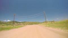 Car driving on rural dirt road in South Denver, near Chatfield State Park Stock Footage