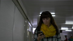 Young woman walking in the underpass looks into the phone, listening to music Stock Footage