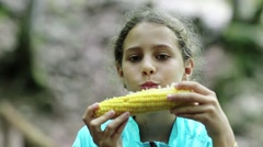 Beautiful girl in blue jacket eats corn and looks around Stock Footage