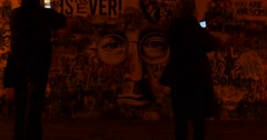 Two people standing in the evening Prague in front of The John Lennon Wall  Stock Footage