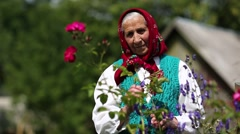 Old woman stands in flowers near his house and looks at the camera Stock Footage