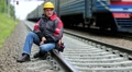 Railway worker sits on railway line HD Footage