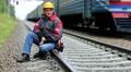 Railway worker sits on railway line HD Footage