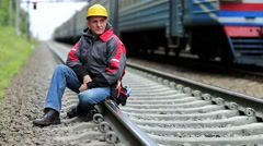 Railway worker sits on railway line Stock Footage