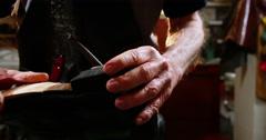 Shoemaker repairing a shoe in workshop 4k Stock Footage