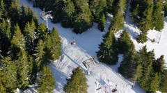 Running ski lift aerial transportation system in dense forest from above Stock Footage