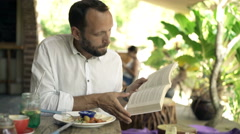 Young man reading book while eating lunch in cafe in the garden, 4K Stock Footage