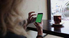 Businesswoman using mobile cell phone with green touch screen in cafe Stock Footage
