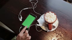 Cup of coffe with marshmellou and women using cellphone with green in cafe Stock Footage