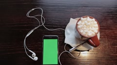 Cup of coffe with marshmellou and cellphone with green in cafe Stock Footage