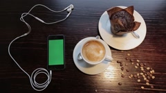 Cup of coffe with marshmellou, muffin and cellphone with green in cafe Stock Footage