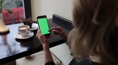 Attractive young woman using her green touch screen mobile cell phone in cafe Stock Footage