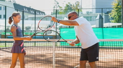 Instructor or coach teaching child how to play tennis on a court indoor Stock Footage