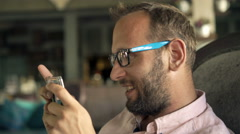 Happy man playing game on smartphone sitting in cafe, 4K Stock Footage