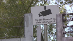 This area is being watched by video surveillance sign at fence 4k Stock Footage