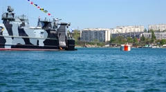 The yacht sails past the warship in the port of Sevastopol. Crimea. Stock Footage