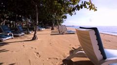 Nusa Dua beach. Deck chairs on a beach near the hotel at the morning. Ocean surf Stock Footage