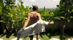 Young man dressing up shirt and looking on the garden, super slow motion Stock Footage