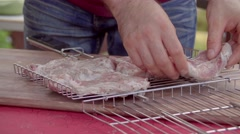 The man displays meat on a lattice. The man cooks meat for frying. The man cooks Stock Footage