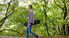 Teenager boy with skateboard walking in the park Stock Footage