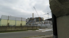 Chernobyl nuclear reactor sarcophagus and memorial from 150 meters Stock Footage