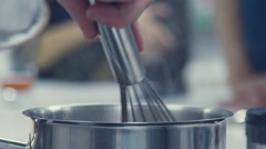 Metal pot on the stove. Whisk for stirring Stock Footage