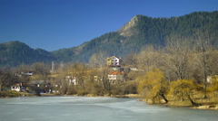 Frozen pond with cottages in forest. Beautiful lakeside village  Stock Footage