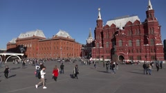 Unidentified citizens walk across city square, slowmo, old red brick buildings Stock Footage