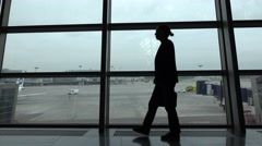 Man pace at airport lounge waiting for flight, empty apron field outside Stock Footage