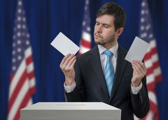 Election in USA. Undecided voter holds envelopes in hands above vote ballot a Stock Photos