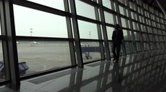 Silhouette view, man walk the floor at airport lounge, waste time wait departure Stock Footage