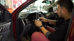 Auto exhibition Man testing Volkswagen car and its dashboard inside the car. Stock Footage