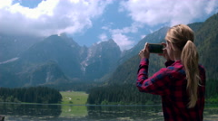Jib shot - Young female hiker taking photos of a nature with her phone Stock Footage