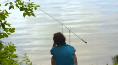 Student girl fisherman is fishing on the bank of the river, lake Stock Footage